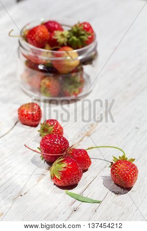 strawberries on white boards in glass jar in background