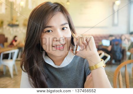 Happy Asian Woman Talking On Cellphone In Hipster Cafe