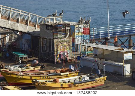 VALPARAISO, CHILE - JULY 5, 2016: Colourful inshore fishing boats on the quayside at the fish market in the UNESCO World Heritage port city of Valparaiso in Chile.
