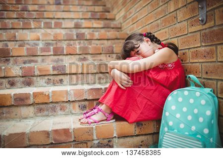 Sad brunette girl seated against a brick wall in the stairs