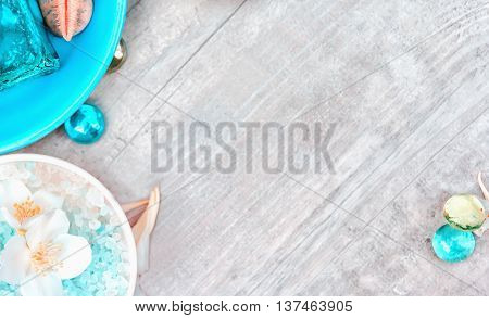 Natural spa background with copy space. Elements of spa accessories and jasmine bath salts against the light wooden background. Blurred selective focus.