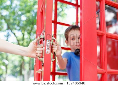 confidential phone conversation in a telephone box. Teenager talking on the phone, the adult tries to intervene. child protects the right to privacy from parents. concept of personal life, misunderstanding between children and parents.