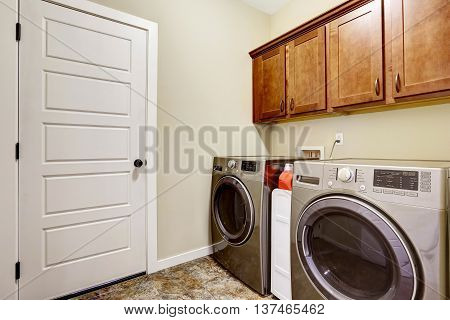 Laundry Room With Steel Appliances And Nice Cabinets