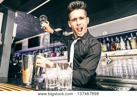 Flair bartender at work in a night club - Barman mixing some cocktail in a bar