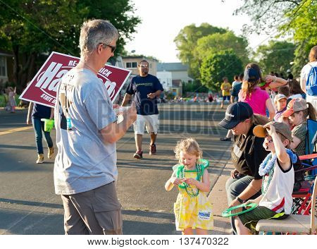 SOUTH ST. PAUL, MINNESOTA - JUNE 24, 2016: Campaign worker hands out literature of local candidates for Minnesota Legislature at annual South St. Paul Kaposia Days Grande Parade on June 24.