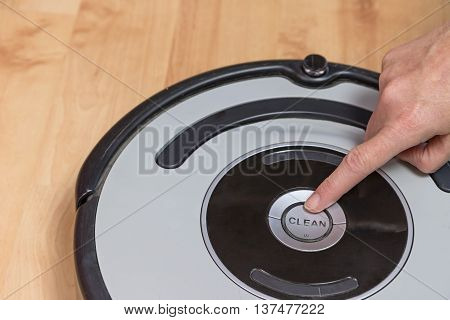 Feminine finger is ready to push button CLEAN on the used robotic vacuum cleaner. All potential trademarks are removed.