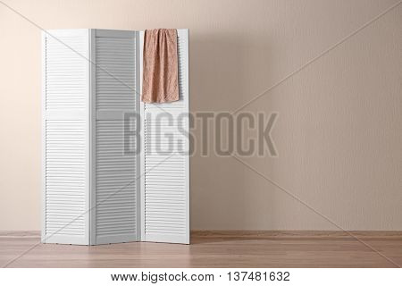 White folding screen with towel in room