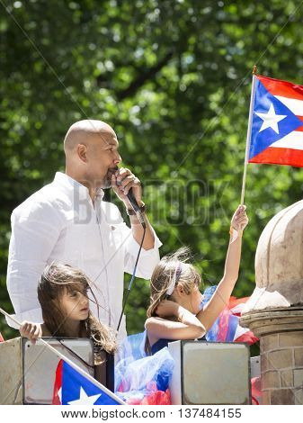 NEW YORK - JUNE 12 2016: Ruben Diaz Jr, Bronx Borough President rides on a float during the 59th annual National Puerto Rican Day Parade on 5th Avenue in New York City on June 12 2016.