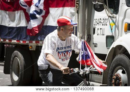 NEW YORK - JUNE 12 2016: A man rides a bicycle adorned with the flag of Puerto Rico during the 59th annual National Puerto Rican Day Parade along 5th Avenue in New York City on June 12 2016.