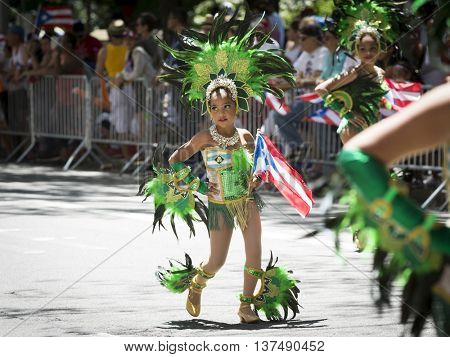 NEW YORK - JUNE 12 2016: Young girls wearing traditional carnival costumes and headdresses dance on 5th Avenue in the 59th annual National Puerto Rican Day Parade in New York City on June 12 2016.