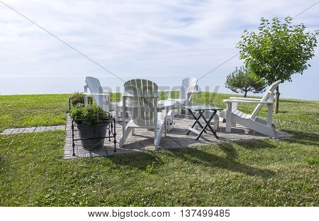 Serene Scene of White Adirondack Chairs by Lake Erie