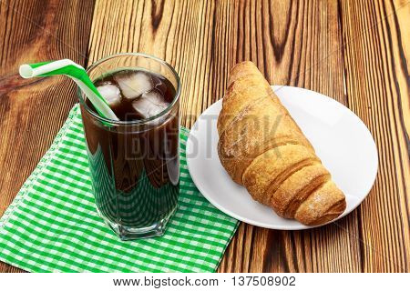 Glassful of black coffee with ice and tubule on green napkin. croissant wooden table in cafe