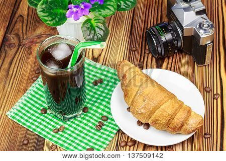 Glassful of black coffee with ice and tubule on green napkin. croissant vintage camera flowerpot wooden table.