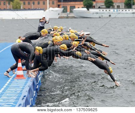 STOCKHOLM - JUL 02 2016: The female competitors weariny yellow bathing cap jump into the water after the start signal in the Women's ITU World Triathlon series event July 02 2016 in Stockholm Sweden