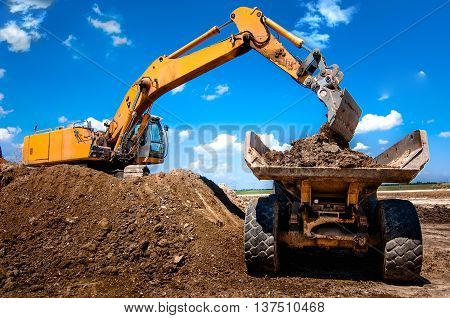 Excavator Loading Dumper Truck Tipper In Sandpit In Highway Cons