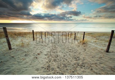 sand path to North sea beach at sundown Holland