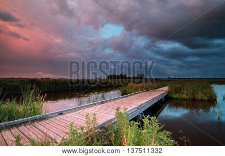 bike road over lake durinf storm at sunset Drenthe Netherlands