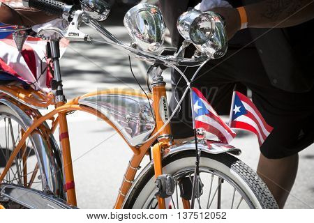 NEW YORK - JUNE 12 2016: A man walks with a bicycle adorned with the flag of Puerto Rico during the 59th annual National Puerto Rican Day Parade along 5th Avenue in New York City on June 12 2016.