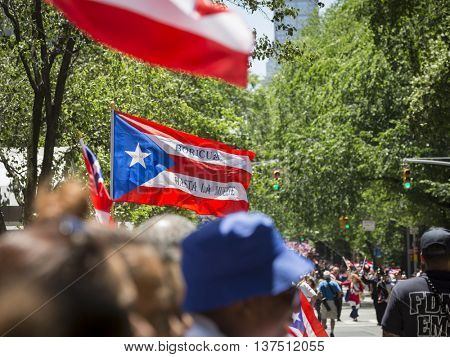NEW YORK - JUNE 12 2016: Spectators celebrating the 59th annual National Puerto Rican Day Parade wave flags from along 5th Avenue in New York City on June 12 2016.