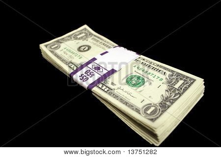 A stack of US one dollar bills isolated against black background
