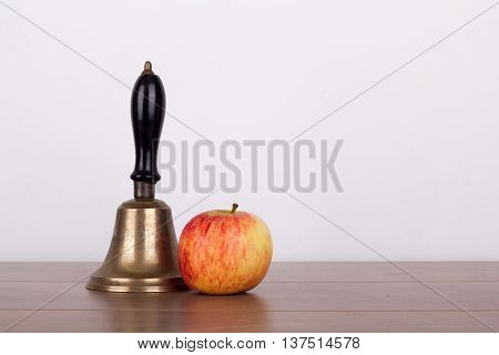Old Fashioned Bell And Apple On A Wooden Surface
