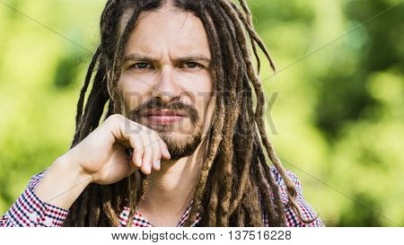 portrait of stern man with dreadlocks on a green background