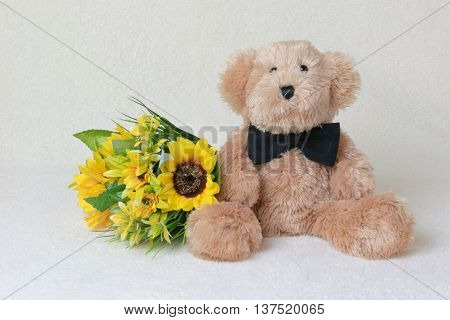 teddy bear with bow tie and flowers