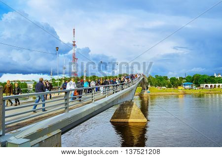 VELIKY NOVGOROD RUSSIA - JUNE 11 2016. Footbridge across the Volkhov river and a lot of tourist people walking along in summer evening on City Day
