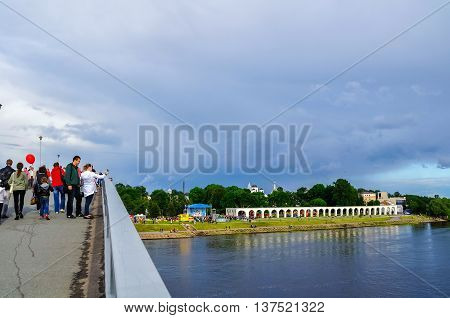 VELIKY NOVGOROD RUSSIA - JUNE 11 2016. City Day in Veliky Novgorod - holiday celebrations and tourist walking on the footbridge across the Volkhov river