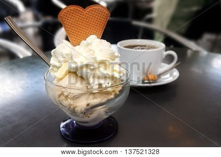 sundae with ice cream whipped cream and biscuit in heart shape and a cup of coffee on a metal table in a shady street cafe