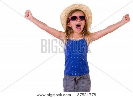 Trendy pretty little girl in a summer outfit and straw hat raising her arms and cheering three-quarter isolated on white