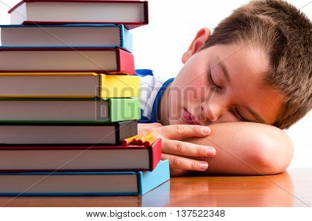 Bored Or Overworked Schoolboy Asleep On His Desk