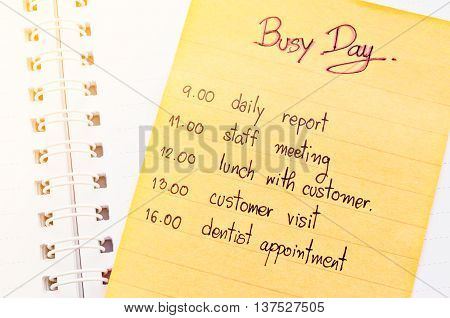 Busy day appointment business schedule in note paper on open diary.
