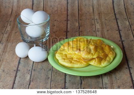 Keto Egg Bread also called Oopsie Bread on a plate with the main ingredient of eggs on the side poster