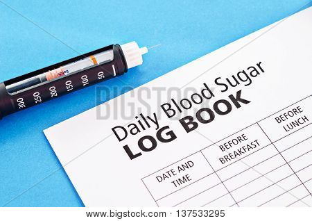 Insulin injection pen with daily blood Log Book on blue background.
