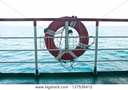 lifebuoy hanging on metal fence of the boat with seascape background