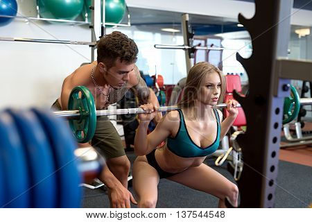 At gym. Image of sexy coach helps girl to do squat