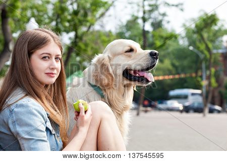 Portrait of a young girl and her dog close up outdoors. Happy owner of eating a green apple and hugs his dog breed golden retriever on a background of summer city. Human friendship and dogs. Joint pastime.