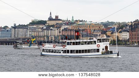 STOCKHOLM - JUL 02 2016: Two steem ferrys used by tourists in central Stockholm old buildings in the background. July 02 2016 in Stockholm Sweden