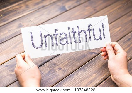 hands hold white paper with word unfaithful