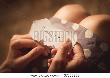 Top view of woman in dotted dress holding a paper message with the text I miss you