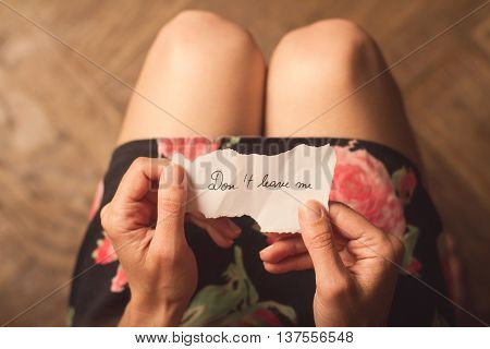 Top view of woman in dark dress holding a paper message with the text do not leave me