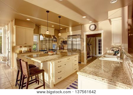 Large Luxury Kitchen Room In Beige Colors With Granite Counter Tops And Tile Floor.
