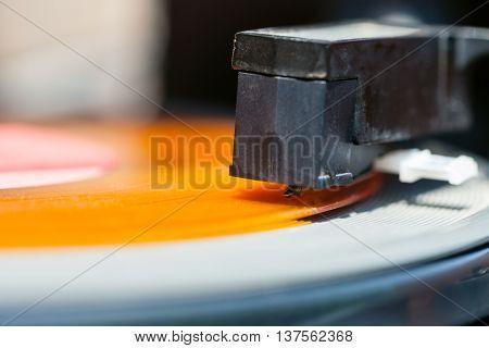 stylus of headshell on orange vinyl record close up
