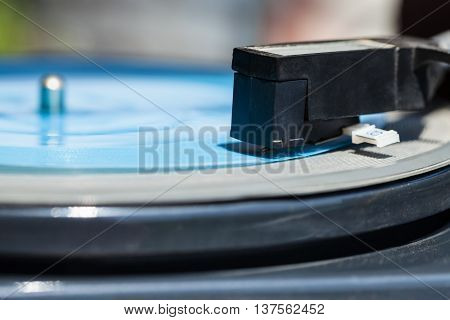 side view of headshell with stylus of turntable on blue flexi disc