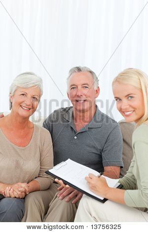 Seniors with doctor looking at the camera at home