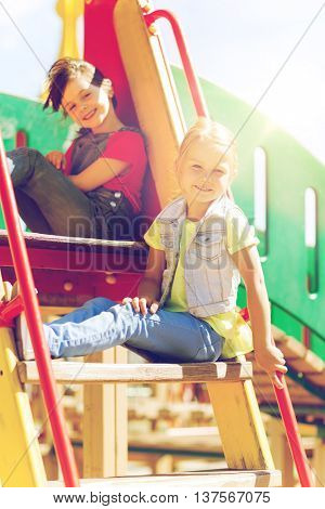 summer, childhood, leisure, friendship and people concept - happy kids or children on playground climbing frame or slide