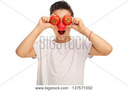 Joyful kid with a red clown nose holding two tomatoes in front of his eyes isolated on white background