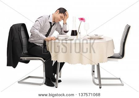 Stood up guy sitting on a restaurant table and waiting for his date isolated on white background