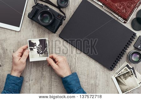 Photography equipment and camera on a desktop a photographer is holding a picture and creating a photo album